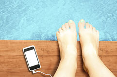 Woman legs with blank screen smartphone at swimming pool - liste Royalty Free Stock Images