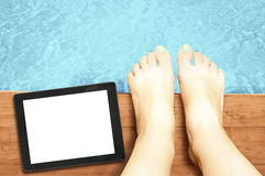 Woman legs with blank screen tablet pc at swimming pool - relaxi Royalty Free Stock Photos