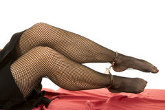 Woman legs blck fishnet cuffs on ankles Royalty Free Stock Photos