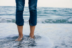 Woman legs in blue jeans standing in the sea water on the coast.  Stock Photo