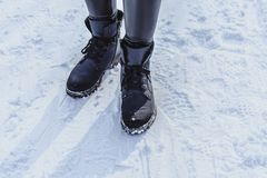 Woman legs in boots on the snow royalty free stock photo