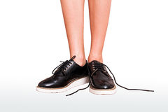 Woman legs in brogue oxford classic shoes. untied shoelace Stock Photo