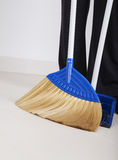 Woman legs with broom and dustpan sweeping floor Royalty Free Stock Photo
