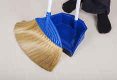 Woman legs with broom and dustpan sweeping floor Stock Photos