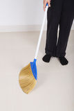 Woman legs with broom sweeping floor Stock Photo