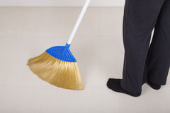 Woman legs with broom sweeping floor Royalty Free Stock Images