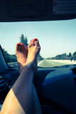 Woman legs on car dashboard Stock Photos