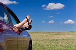Woman legs in car window Stock Photos
