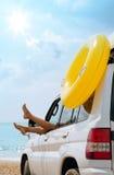Woman legs in car window. At sea beach Stock Image