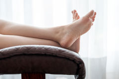 Woman legs on the chair Stock Images
