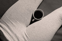 Woman legs and coffee. Girl drinking a cup of coffee on a sofa, grey leggings Stock Photo