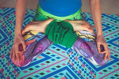 Woman legs in colorful leggings in lotus pose from above view in Stock Photo