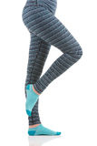 Woman legs in colourful striped thermal pants and blue socks from the side view standing on one leg with other led raised Royalty Free Stock Photos