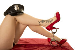 Woman legs with cop hat on knee red heels and tattoo Royalty Free Stock Photography