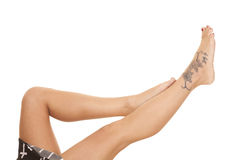 Woman legs crosses tattoo lay feet up Stock Photos