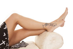Woman legs crosses tattoo lay Stock Image