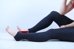 Woman legs and a cup of tea Stock Photography