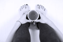 Woman legs and a cup of tea Royalty Free Stock Photo