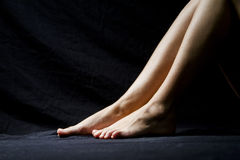 Woman legs with dark background Stock Photography