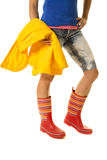 Woman legs in denim shorts and boots hold yellow raincoat side Stock Photography