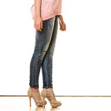 Woman legs in denim trousers high heels shoes Stock Photos