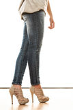 Woman legs in denim trousers high heels shoes Stock Photography