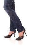 Woman legs dressed in jeans. And black shoes walk forward over white background Stock Photography