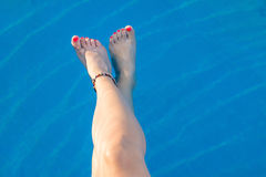 Woman legs while enjoying at the pool. Woman legs while enjoying at the swimming pool Stock Images