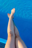 Woman legs while enjoying at the pool. Woman legs while enjoying at the swimming pool Royalty Free Stock Image
