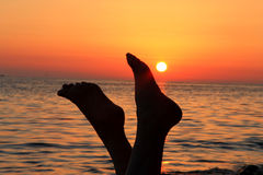 Woman legs and evening beach on the sunset. A Naked woman legs and evening beach on the sunset Royalty Free Stock Image
