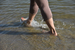 Woman legs and feet walking in the water royalty free stock image
