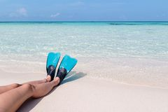 Woman legs with flippers on a white beach in the Maldives. Crystal clear blue water as background. Holiday in paradise concept. woman relaxing on the beach and stock image