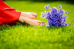 Woman legs on green grass with flower dress. Summer vacation concept. backlit stock photography