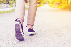 Woman legs gumshoes. Sunny woman legs gumshoes walk Stock Photos