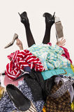 Woman legs and hands reaching out from a big pile of clothes and accessories. Woman buried under an untidy cluttered woman wardrobe. Woman in high heels needs