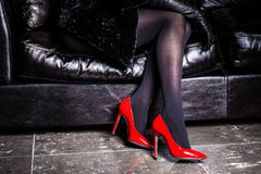 Woman legs with heels pointing up isolated on a couch. Beautiful woman legs with stockings and heels pointing up isolated on a couch. Girl in dress royalty free stock image