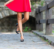 Woman legs with heels and red skirt Stock Images