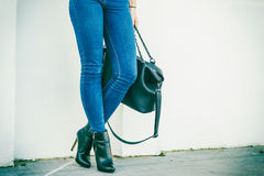 Woman legs in heels shoes handbag in hand Stock Image
