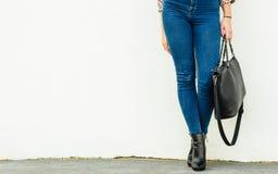 Woman legs in heels shoes handbag in hand Stock Photos