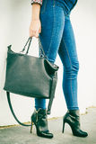 Woman legs in heels shoes handbag in hand Royalty Free Stock Photography