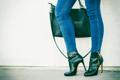 Woman legs in heels shoes handbag in hand. Autumn fashion outfit. Fashionable woman long legs in denim pants black stylish high heels shoes and handbag outdoor Royalty Free Stock Images