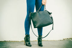 Woman legs in heels shoes handbag in hand Royalty Free Stock Images