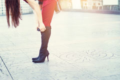 Woman legs in high heels black boots on street background, soft Royalty Free Stock Photography