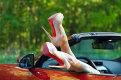 Woman legs in high heels out the windows in car Stock Photo