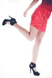 Woman legs in high heels and red dress. Stylish young woman wear fashionable clothes. Long legs in black high heels. Girl in short red dress Stock Photos