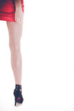 Woman legs in high heels and red dress. Stylish young woman wear fashionable clothes. Long legs in black high heels. Girl in short red dress Stock Images