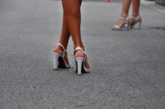 Woman legs with high heels. Woman legs with white high heels walking on the street Royalty Free Stock Image