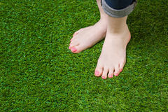 Woman legs injeans standing  on green grass Royalty Free Stock Images