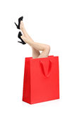 Woman legs inside a shopping bag Stock Photography