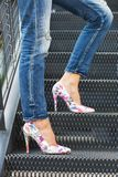 Woman legs in jeans and colorful sexy high heels, standing on a staircase, photographed from the side royalty free stock photography